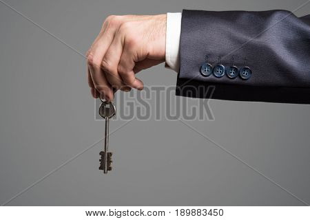 Man in the suit holding key in hand.