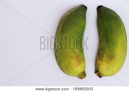 Bananas that are going to be cooked are greenish yellow on a white background