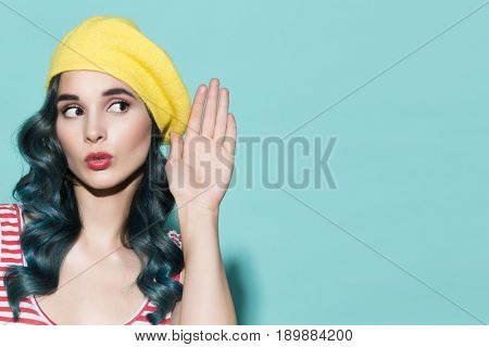 Beautiful woman in a yellow beret listening. On a blue background.