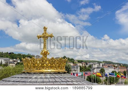 Golden cross and crown and beautiful sky in Lourdes, France, Hautes Pyrenees. Basilica of our Lady of the Rosary