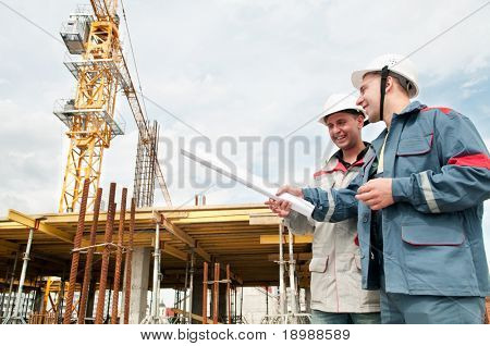 Two engineer builders with blueprint at construction site