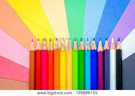 Close up macro shot of sharp colorful pencils lined up in a row on colorful paper sheets