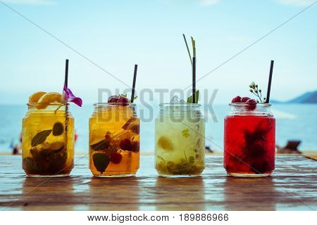 Set of iced cocktails: with lemongrass, berries, strawberry, peach, mint decorated with flower, grass on sea beach background.