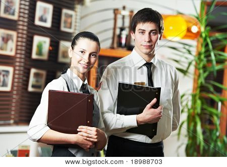 Waitress girl and waiter man of commercial restaurant in uniform waiting an order with menu