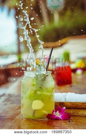 Close up of glass with tropical refreshing lemongrass coctail with mint, ginger and flower decoration with splashes on palm beach bar background.