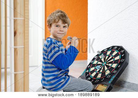 Little cute blond preschool kid boy playing dart, indoors. Happy child having fun with dartboard, winning game.
