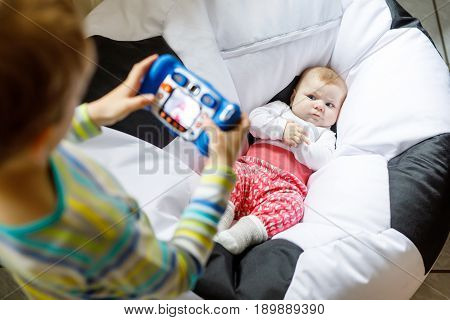 Little kid boy taking picture with toy camera of cute baby girl. Brother and little tiny sister having fun together. Memories for family album. Two children playing.