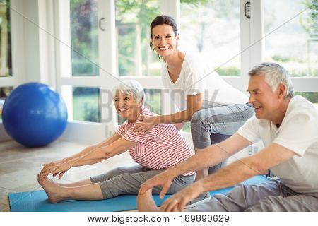 Female trainer assisting senior couple in performing exercise at home