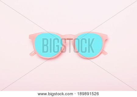 Stylized pink sunglasses with blue lens on a pink background. Background and lens can be used as a place for text on summer themes