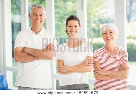 Female trainer and senior couple standing together with arms crossed at home