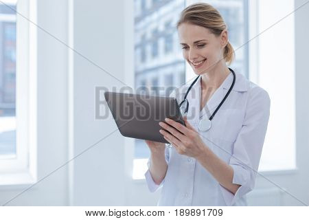 Always exploring new professional horizons. Concentrated lively professional practitioner enjoying working hours in the hospital while expressing interest and using tablet