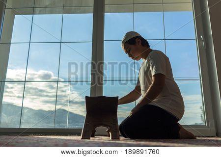 Muslim boy reading Quran and praying for god