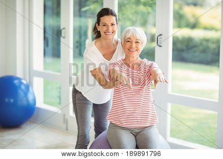 Female coach assisting senior woman in performing exercise at home