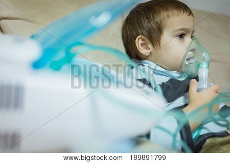 Beautiful sick boy inhalation therapy by the mask of inhaler. Image of a cute kid with respiratory problem or asthma. View of nebulizer with smoke from oxygen mask
