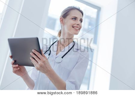 Using gadgets for professional issues. Upbeat happy professional doctor enjoying working hours at the hospital while expressing positivity and using tablet