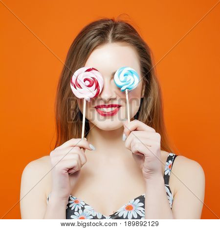 Funny Girl Covers Her Eyes with Two Lollipops on Orange Background. Attractive Brunette with Red Lips and Candy in Studio.