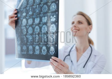 Providing qualified body examination. Qualified glad diligent radiologist working at the clinic while examining x ray and analyzing diagnose verdict