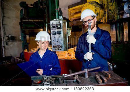 A portrait of factory workers operating a lathe