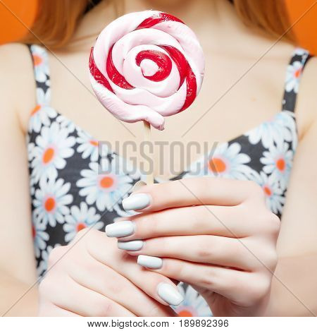 Female Hands Holding Big Colorful Lollipops on Orange Background in Studio.