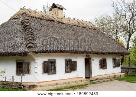 Ancient peasant Ukrainian house in the spring with a thatched roof in the old village of national architecture Ukraine. National Museum Pirogovo in the outdoors near Kiev.