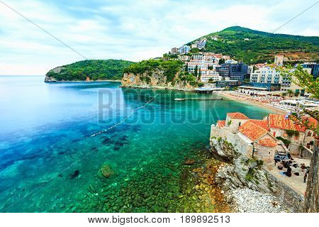 Sea landscape and beautiful cityscape. Rocky island and shoreline in cloudy evening. Old Town of Budva, medieval walled city, bay, mountains, coastal strip, sandy beaches on Adriatic Sea, Montenegro.