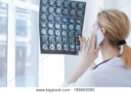 Analyzing brain checkup. Concentrated skilled experienced radiologist working at the x ray cabinet while holding brain x ray and using electronic gadget for conversation