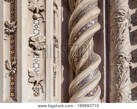 Element of the arch portico with leaves of fig, grape, oak and gold mosaic. Catholic Cathedral, architecture of the Middle Ages in the Umbria region, Italy