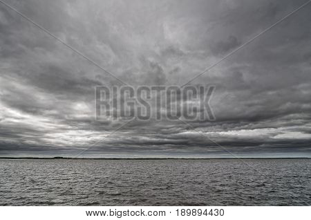 Cloudy sky and dark water on the river Volga