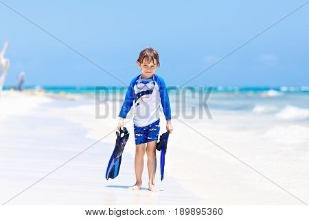 Adorable little blond kid boy having fun on tropical beach of Boracay, Philippines. Excited child playing and surfing in sun protected swimsuit in ocean on vacations. White sand, Kid holding flippers