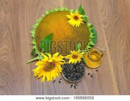 Sunflower seeds flowers and oil on a wooden background. Horizontal photo.