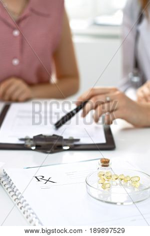 Medical prescription form, capsules and pills are lying against the background of a doctor and patient discussing health exam results.