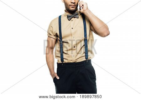 cropped view of man wearing in suspenders and bow tie using smartphone isolated on white