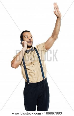 african american man waving and using smartphone wearing in suspenders and bow tie isolated on white