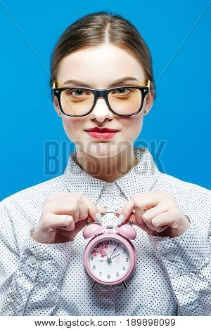 Young Woman with Ponytail Holding Pink Alarm Clock in Hands in Studio on Blue Background. Time Concept.