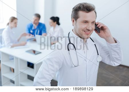 Full of happy emotions . Positive delighted experienced doctor working at the clinic and enjoying conversation on the phone while colleagues enjoying conversation in the background