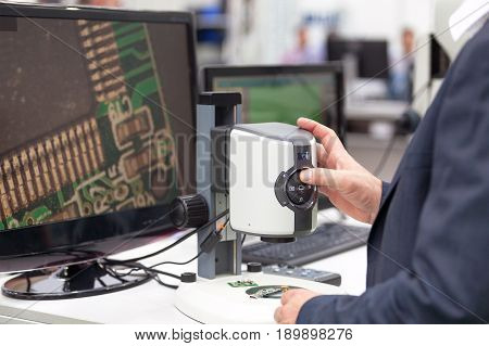 Operator working with digital microscope, inspecting electronic component