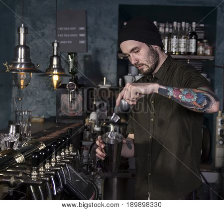 Bartender is making a cocktail in a bar