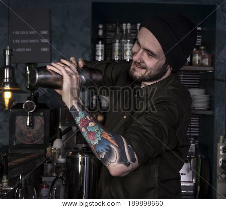 smiling bartender is mixing a fancy cocktail