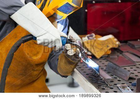 Welder in action. Worker with protective mask welding metal.