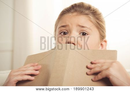 Frightened Adorable Schoolgirl Holding Book And Looking At Camera At Home