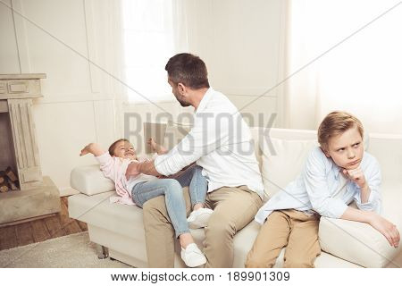 offended boy sitting on sofa while his father tickling daughter behind