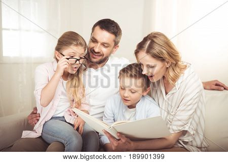 Happy family with two children sitting on sofa and reading book together