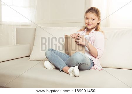 Casual Girl Holding Book And Smiling At Camera While Sitting On Sofa At Home