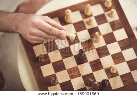 Partial View Of Hand Of Chess Player Making A Move Of Check Mate During Game