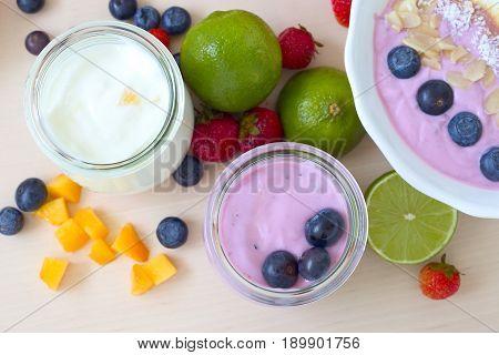 Yogurt dessert with fruits: blueberries, lime, mango and strawberries.