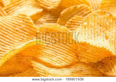 Yellow salted potato chips as background, closeup. Chips texture studio photo
