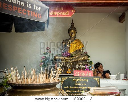 BANGKOK, THAILAND - MAY 05, 2017: The Buddha statue with a poor man sitting nearby Buddha waiting for someone.