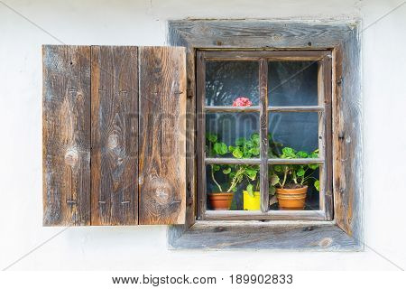 An old antique window with flowers in a vintage peasant white house in Ukraine. An antique wooden window frame with a door. Ancient peasant Ukrainian house in the spring with a thatched roof in the old village of national architecture Ukraine.