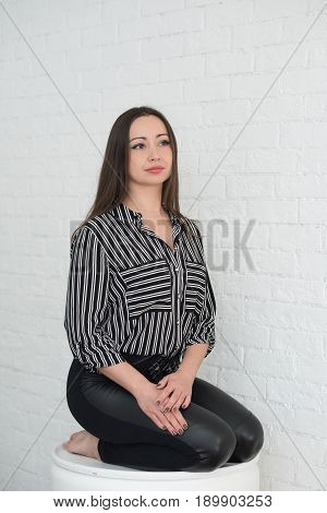 A beautiful brunette girl with long hair large brown clasps and long eyelashes in a striped blouse and leather leggings sits on her lap against a white brick wall and looks thoughtfully into the distance.