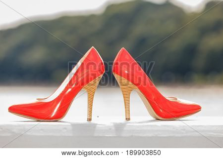 Feminine footwear outfit accessories concept. Detailed closeup of red high heels shoes